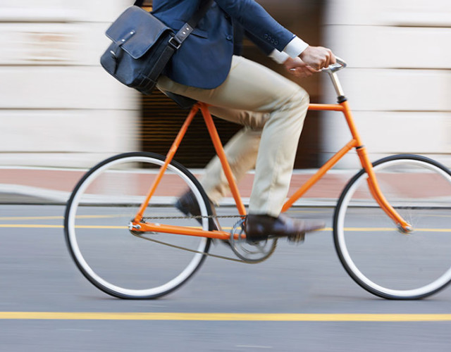 man riding orange bicycle