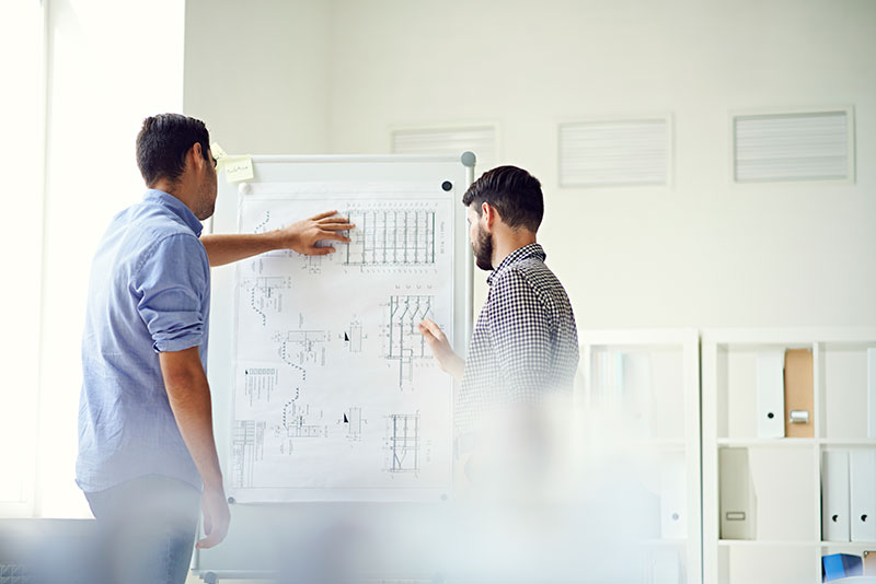 man overlooking blueprint of project